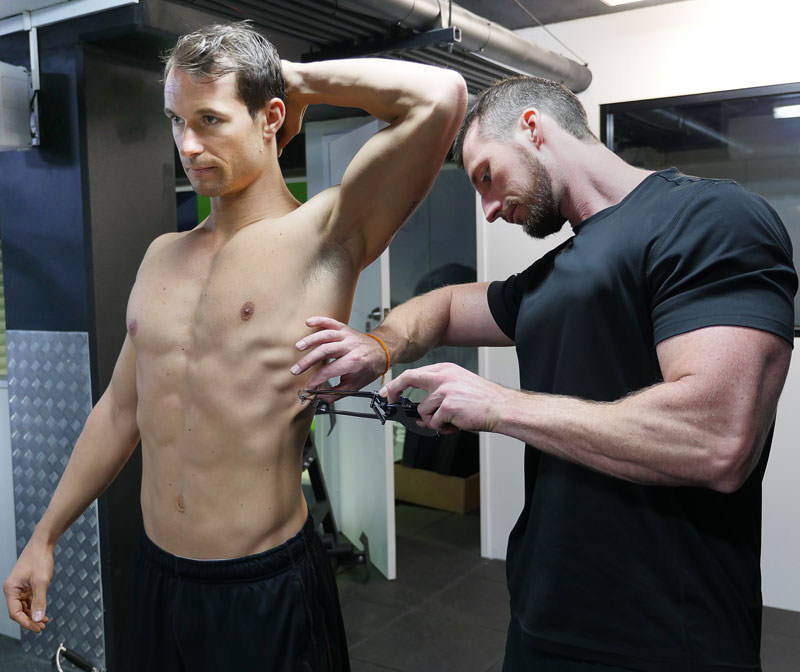 Tom Hewett performing a body fat pinch with client Pauly